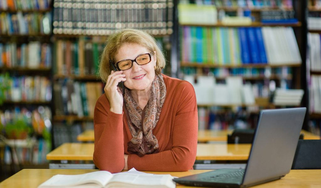 senior woman using mobile phone in library.